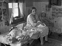 0121103 © Granger - Historical Picture ArchiveMISSOURI: CABIN, 1936.   A mother nursing her baby and seated on a cot beside her young daughter in the Ozark Mountains, Missouri. Photograph by Carl Hydans, May 1936.