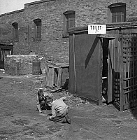 0121149 © Granger - Historical Picture ArchiveMARBLE GAME, 1936.   Two boys playing marbles, next to an outhouse in St. Louis, Missouri. Photograph by Arthur Rothstein, March 1936.