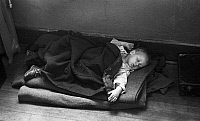 0122201 © Granger - Historical Picture ArchiveFLOOD REFUGEE, 1937.   A young flood refugee sleeping on the floor in a makeshift bed inside a schoolhouse, Sikeston, Missouri. Photograph by Russell Lee, January 1937.
