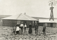 0130678 © Granger - Historical Picture ArchiveNEBRASKA: SETTLERS, c1885.   Family of homesteaders, photographed outside of their sod house with a windmill on the roof of the adjoining building in Custer County, Nebraska. Photograph by Solomon D. Butcher, c1885.