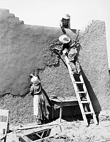 0033288 © Granger - Historical Picture ArchiveNEW MEXICO: ADOBE HOUSE.   Replastering an adobe house at Chamisal, New Mexico. Photograph, 1940, by Russell Lee.