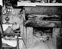 0122318 © Granger - Historical Picture ArchiveBOY READING, 1940.   A farmer's son reading in front of a fireplace in a dugout home, Pie Town, New Mexico. Photograph by Russell Lee, June 1940.