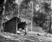 0621813 © Granger - Historical Picture ArchiveADIRONDACKS: CABIN, c1909.   A lean-to cabin on Raquette Lake in the Adirondacks, New York. Photograph, c1909.