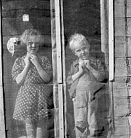 0123518 © Granger - Historical Picture ArchiveFARM CHILDREN, 1939.   A sister and brother standing behind a screen door of their farm home in Dead Ox Flat, Malheur County, Oregon. Photograph by Dorothea Lange, October 1939.