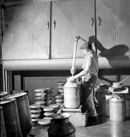 0324395 © Granger - Historical Picture ArchiveVERMONT: CREAMERY, 1941.   A worker fills a milk can with cream as it exits a cooling unit in the United Farmers' Cooperative Creamery in Sheldon Springs, Vermont. Photograph by Jack Delano, September 1941.