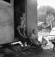 0123718 © Granger - Historical Picture ArchiveFARM FAMILY, 1939.   The oldest girl seated in the doorway of the house trailer cares for her sisters while her parents are working on the farm, Yakima Valley, Washington State. Photograph by Dorothea Lange, August 1939.