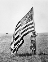 0130951 © Granger - Historical Picture ArchiveWISCONSIN: PATRIOTISM.   A patriotic young woman posing with the American flag on the Wisconsin prairie, c1900.