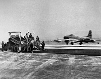 0102468 © Granger - Historical Picture ArchiveKOREAN WAR: U.S. AIR FORCE.   A U.S.A.F. F-80 Shooting Star takes off from a South Korean airstrip as a construction crew of the 931st Engineer Aviation Group puts down an asphalt surface, c1952.