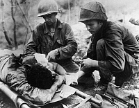 0102544 © Granger - Historical Picture ArchiveKOREAN WAR: WOUNDED, 1952.   An Allied soldier, wounded in the battle for 'Old Baldy,' receives first aid from two medical corpsmen, August 1952.