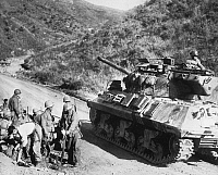 0102638 © Granger - Historical Picture ArchiveKOREAN WAR: CIVILIANS.   On the west-central front in Korea an American tank passes an improvised aid station where Koreans receive first aid, October 1952.