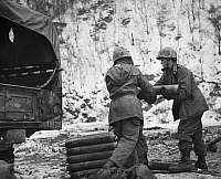 0102640 © Granger - Historical Picture ArchiveKOREAN WAR: ROCKETS.   U.S. Marines piling rockets for the 24-rail T66 rocket launcher on the Korean front, early 1950s.
