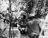 0039077 © Granger - Historical Picture ArchiveVIETNAM WAR: U.S. MARINES.   Fifth Regiment, First Marine Division fire team wading through water on a search and clear operation near the demilitarized zone in Vietnam, December 1966.