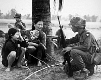 0039078 © Granger - Historical Picture ArchiveVIETNAM WAR: INTERPRETER.   An interpreter questions the family of a Viet Cong suspect as Infantrymen of the 1st Brigade, 101st Airborne Division, look on, February 1966.