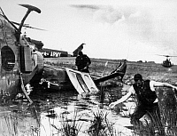 0102410 © Granger - Historical Picture ArchiveVIETNAM: DOWNED HELICOPTER.   The crew of an American helicopter, shot down in a flooded rice paddy in South Vietnam by Viet Cong ground forces, search for weapons, September 1964.