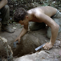 0528197 © Granger - Historical Picture ArchiveVIETNAM WAR, 1967.   Sergeant Ronald Payne checking a tunnel for Viet Cong in the Ho Bo Woods. Photograph, 24 January 1967.