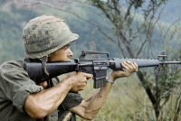 0528225 © Granger - Historical Picture ArchiveVIETNAM WAR, 1967.   Private Michael Mendoza firing a M-16 rifle in the direction of sniper fire. Photograph, 8 September 1967.