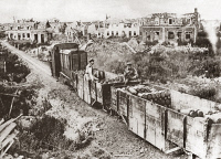 0407998 © Granger - Historical Picture ArchiveWORLD WAR I: ARMORED TRAIN.   A Canadian armored train bearing ammunition to the front line of fighting through a ruined village during World War I. Photograph, c1916.