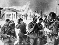 0017931 © Granger - Historical Picture ArchiveWORLD WAR II: SOVIET UNION.   German soldiers pausing for a rest in front of a burning Russian town, February 1941.