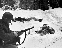 0017946 © Granger - Historical Picture ArchiveWORLD WAR II: U.S. TROOPS.   An American infantryman loads his rifle while advancing on the front line near Houffalize, Belgium. Two dead German soldiers are in the background, 1940s.