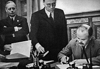 0033786 © Granger - Historical Picture ArchiveNAZI-SOVIET PACT, 1939.   Soviet Foreign Minister Vyacheslav Molotov signing the Nazi-Soviet Non-Aggression Pact, 23 August 1939, in Moscow, Russia, at the start of World War II. Another singnatory, German Minister of Foreign Affairs Joachim von Ribbentrop (far left), looks on.