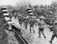 0045824 © Granger - Historical Picture ArchiveWWII: WEST FRONT, 1945.  U.S. Infantrymen of the 90th Division pass concrete dragon's teeth of the Siegfried Line of Habscheid, Germany, as they move to the front in February 1945.