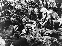 0080099 © Granger - Historical Picture ArchiveWORLD WAR II: MEDIC, 1944.   A medic administers first aid to a wounded marine on Cape Gloucester, New Britain, during World War II, February 1944.