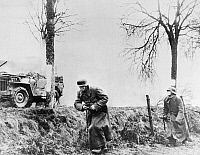 0099925 © Granger - Historical Picture ArchiveWORLD WAR II: COMBAT, 1944.   German soldiers file past a burning American half-track. Photographed 17 December 1944.