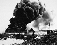 0100278 © Granger - Historical Picture ArchiveWORLD WAR II: MIDWAY, 1942.   Oil tanks burn after being attacked by Japanese warplanes at the U.S. Naval Air Station on Sand Island, Midway atoll, during the Battle of Midway, 4 June 1942.
