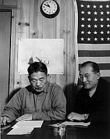 0115085 © Granger - Historical Picture ArchiveJAPANESE INTERNMENT, 1943.   Roy Takeno (right), editor of the Manzanar 'Free Press,' photographed with the 'mayor' of Manzanar at a Town Hall meeting at the Manzanar Relocation Center for Japanese Americans, near Owens Valley, California. Photograph by Ansel Adams, 1943.