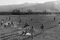0115244 © Granger - Historical Picture ArchiveJAPANESE INTERNMENT, 1943.   Young men playing football at the Manzanar Relocation Center for Japanese Americans, near Owens Valley, California. Photograph by Ansel Adams, 1943.