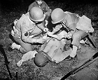 0120542 © Granger - Historical Picture ArchiveFIRST AID DEMONSTRATION.   Demonstration of the proper method for treating abdominal wounds on the battlefield. Photographed at the Presidio in San Francisco, California, 1943, during World War II.