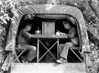 0122686 © Granger - Historical Picture ArchiveWORLD WAR II: SIGNAL CORPS.   A Signal Corps message center set up in the back of a military truck during a field problem at Fort Riley, Kansas. Photograph by Jack Delano, April 1942.