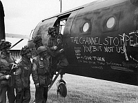 0167152 © Granger - Historical Picture ArchiveWORLD WAR II: WAR PAINT.   Camouflaged British soldiers admire the slogans painted on the side of an airplane, before the invasion of Normandy, June 1944.