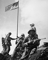 0167342 © Granger - Historical Picture ArchiveWORLD WAR II: IWO JIMA.   The raising of the first flag on Mount Suribachi, Iwo Jima, 23 February 1945. The soldiers are Sergeant Henry Hansen (without helmet), Sergeant Ernest Thomas (seated by flagpole), Corporal Charles Lindberg (standing at right), and Private First Class James Michels (on guard with carbine).