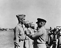 0167343 © Granger - Historical Picture ArchiveWWII: FLYING CROSS AWARDS.   Brigadier General Benjamin Oliver Davis, Sr. pins the Distinguished Flying Cross on his son, Benjamin O. Davis, Jr., while Joseph Elsberry, Jack Holsclaw, Clarence Lester await their turn, in Italy, 1944.