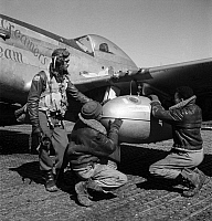 0167421 © Granger - Historical Picture ArchiveWWII: TUSKEGEE AIRMEN, 1945.   Edward Gleed and two other Tuskegee Airmen adjust an external 75 gallon drop tank on the wing of a P-5/D fighter plane 'Creamer's Dream,' at Ramitelli Airfield, Italy. Photograph by Toni Frissell, March 1945.