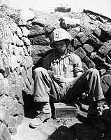 0183635 © Granger - Historical Picture ArchiveWWII: IWO JIMA, 1945.   Portrait of U.S. Marine PFC Keith A. Cole sitting in a foxhole on Iwo Jima. Photograph, 1 March 1945.