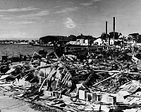 0216443 © Granger - Historical Picture ArchiveWWII: PHILIPPINES, 1941.   View of the damaged Cavite Navy Yard in the Philippines after the Japanese air attacks, showing the remains of the post office and the wrecked submarine USS Sealion at the dock in the foreground. Photograph, 17 December 1944.