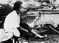 0216466 © Granger - Historical Picture ArchiveWWII: PHILIPPINES, 1945.   An injured Filipino woman and her baby waiting for rescue in Manila, Philippines during the Battle of Manila. Photograph, 1945.