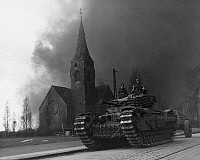 0216516 © Granger - Historical Picture ArchiveWWII: BRITISH TANK, 1945.   A British Churchill flame throwing tank in Sterkrade, Germany, against a background of smoke from the synthetic oil refineries set afire by American troops three days earlier. Photograph, 31 March 1945.
