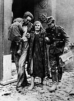 0216658 © Granger - Historical Picture ArchiveWORLD WAR II: BERLIN, 1944.   A man, woman and child are helped by a soldier through the rubble on a street in Berlin, following Allied air strikes. Photograph, 1944.