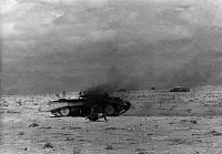 0323660 © Granger - Historical Picture ArchiveWORLD WAR II: NORTH AFRICA.   A burning British tank after being hit during the army's Operation Crusader outside of Tobruk, Libya. One crew member is escaping. Photograph, August 1941. Full credit: Eric Borchert - ullstein bild / Granger, NYC -- All Rights Reserved.