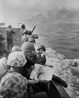 0409718 © Granger - Historical Picture ArchiveWWII: MARINES, 1943.   American marines at leisure on a landing barge as it approaches the Japanese-held island of Tarawa, Gilbert Islands. Tarawa burns in the background. Photograph, 1943.