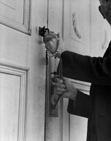 0529051 © Granger - Historical Picture ArchiveJAPANESE INTERNMENT, 1942.   Reverend Naito, a Buddhist priest, locking the doors to his church in Florin, California, as he prepares to be relocated to an internment camp for the duration of the war. Photograph by Dorothea Lange, 12 January 1942.
