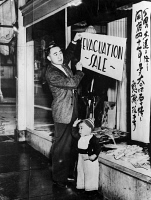 0621690 © Granger - Historical Picture ArchiveJAPANESE INTERNMENT, 1942.   A Japanese American merchant in San Francisco, posting a sale sign in preparation for evacuation to an internment camp during World War II. Photograph, c1942.