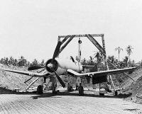 0621757 © Granger - Historical Picture ArchiveWWII: FIGHTER PLANE, 1943.   The tail of a United States Marine Corps fighter plane is hoisted up as mechanics line up the sights of the guns. Photographed in the Solomon Islands during World War II, 1943.