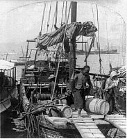 0113931 © Granger - Historical Picture ArchiveCHINESE JUNK, c1900.   Two men on a Chinese junk boat unloading a barrel in Hong Kong, China. Stereograph, c1900.