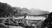 0114615 © Granger - Historical Picture ArchiveCHINA: SUSPENSION BRIDGE.   A Chinese built suspension bridge with boats docked at a pier, Szechwan Province, China. Photograph, c1890-1923.