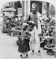 0114862 © Granger - Historical Picture ArchiveCHINA: MUSICIAN, c1900.   An Indian street musician with his daughter, Hong Kong, China. Stereograph c1900.