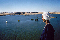0129879 © Granger - Historical Picture ArchiveEGYPT: NILE SCENE.   A man standing beside a flooded expanse of the Nile River in Nubia, Egypt, following construction of the Aswan Dam. Photographed c1970.